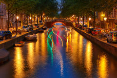 Night city view of Amsterdam canal and luminous track from the b Stock Photos
