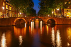 Night city view of Amsterdam canals and seven bridges Stock Photos