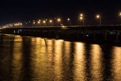 Night cityscape on river in black and gold tone. Royalty Free Stock Image