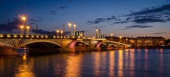 Night cityscape with river and bridge in Saint-Petersburg. Lantern lights on the bridge Stock Photos
