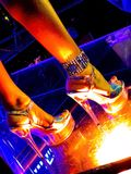 At the night club. Pretty woman legs on the glassy night club floor Royalty Free Stock Photography