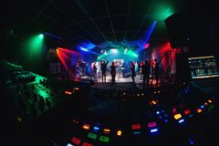 Night club with dancing people on dance floor and stage for musical event and mixer DJ. Night club with dancing people on the dance floor and stage for musical Stock Photos