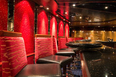 Night club. Modern and elegant bar in a night club on the ship. Red chairs and lights Stock Photography