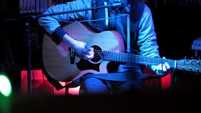 Night club - musician on concert plays acoustic guitar. Close-up telephoto shot stock video footage