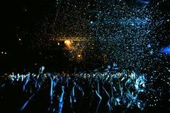 Night club silhouette crowd in confetti. Cheering night club crowd in front of stage and confetti stock photo
