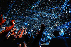 Night club silhouette crowd in confetti. Cheering night club crowd in front of  stage and confetti Stock Photography