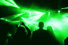 Night club silhouette crowd in front of bright stage lights. Cheering night club crowd in front of  stage lights Royalty Free Stock Image