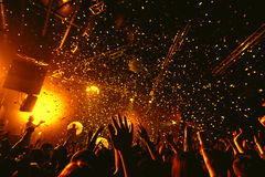 Night club silhouette crowd hands up at confetti stage. Cheering night club crowd at concert with confetti Stock Images