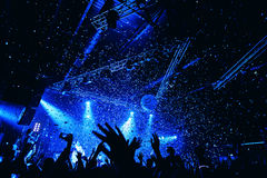 Night club silhouette crowd hands up at confetti stage. Cheering night club crowd at confetti concert Stock Images