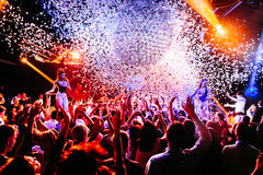 Night club silhouette crowd hands up at confetti steam stage Stock Images