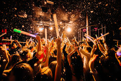Night club silhouette crowd hands up at confetti steam stage stock photography