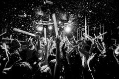 Night club silhouette crowd hands up at confetti steam stage. Cheering night club crowd at fog confetti concert Royalty Free Stock Images