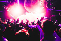 Night club silhouette crowd hands up at confetti steam stage. Cheering night club crowd at fog confetti concert Royalty Free Stock Photos