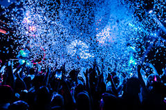 Night club silhouette crowd hands up at confetti steam stage. Cheering night club crowd at fog confetti concert Royalty Free Stock Photo