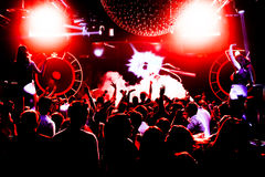Night club silhouette crowd hands up at confetti steam stage. Cheering night club crowd at fog confetti concert Royalty Free Stock Photography