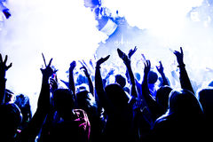 Night club silhouette crowd hands up at confetti steam stage. Cheering night club crowd at fog confetti concert Stock Photos