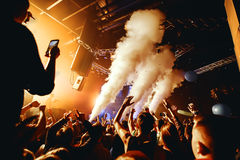 Night club silhouette crowd hands up at steam stage. Cheering night club crowd at fog concert Stock Image