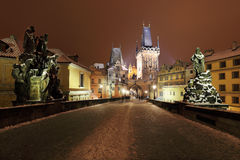 Night colorful snowy Prague bridge Tower with Sculptures from the Charles Bridge royalty free stock photography