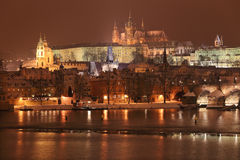 Night colorful snowy Prague gothic Castle with Charles Bridge, Czech Republic Stock Photography