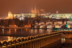 Night colorful snowy Prague gothic Castle with Charles Bridge, Czech Republic Stock Photo