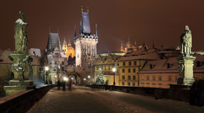 Night colorful snowy Prague gothic Castle and St. Nicholas' Cathedral from Charles Bridge, Czech republic Stock Images