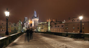 Night colorful snowy Prague gothic Castle and St. Nicholas' Cathedral from Charles Bridge, Czech republic Stock Photos