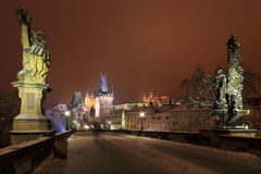 Night colorful snowy Prague gothic Castle and St. Nicholas' Cathedral from Charles Bridge, Czech republic Royalty Free Stock Images
