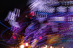 Synthwave disco lights funfair fairground Night colors of the amusement park. Lights moving, light trails, slow shutter-speed royalty free stock image