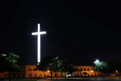 Night Cross. Religious cross lit up at night over a church with floodlights Stock Photography