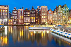 Night dancing houses at Amsterdam, Netherlands. Beautiful typical Dutch dancing houses and tourist boats at the Amsterdam canal Damrak at night, Holland Stock Photo