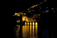Night dark views of medieval stone fortress, which is reflected in the cold black and dark waters the mediterranean sea. Night dark views medieval stone fortress stock photos