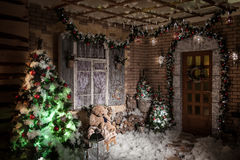 Night in decorated winter patio. Yard of brick house decorated Christmas tree and wreath, New Year ornaments and lights Stock Photo
