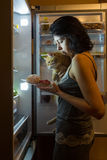 Night desire to eat. Woman and cat at night looking for food in the fridge Stock Photography