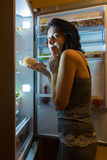 Night desire to eat. Woman secretly takes a night in the fridge sweet food Royalty Free Stock Photo