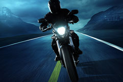 Night Drive. Motorcyclist drives on an empty road in front of a mountain landscape Royalty Free Stock Photos