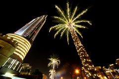 Night Dubai palms with decor lamps and skyscraper Royalty Free Stock Photos