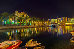 The night in Eilat. The scenic night view of marina with the bright lights, reflected in water, Eilat, Israel Royalty Free Stock Image