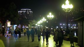 Night embankment of Yalta. Crimea. People tourists walk along the road lit by street lamps stock footage