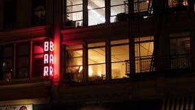 Night exterior establishing shot of apartments over Manhattan bar. A night exterior (DX) establishing shot of typical apartments above a bar and restaurant in stock video footage
