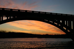 Night falls. A sunset as seen under the arch of a road bridge stock images