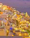 Night in Fira Santorini, Greece. An image of colorful Thira or Fira in Santorini Greece after sunset showing houses in the cliff and restaurants and the Greek stock photos