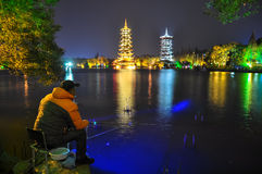 Night fisherman on the background of the Sun and Moon Pagodas Stock Photos