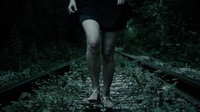 Night, fleeing legs frightened girl. Railway track in forest. Shooting the running away legs of a girl who runs in the dense forest along the railway track stock footage