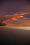 Night Flight. Flight of an airplane (wing) at dusk (sunset Stock Photos