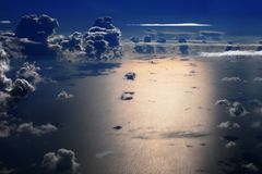 Night flight over the sea. Aerial view of sea and cumulus clouds at night Royalty Free Stock Image