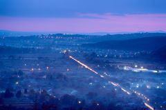 Night foggy landscape. Scenic view to the foggy night landscape with small city, illuminated road and beautiful sunset sky Royalty Free Stock Images