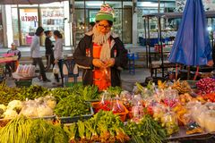Night food market in Thailand, traditional asian market. Sell ready made food, fruits, vegetables, nuts, fish, meat and grocery. People sell and buy green and stock photography