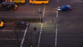 Night footage of people crossing road using a tilt shift effect. stock footage