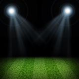 Night football arena illuminated by spotlights Stock Photos