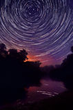 Night forest and lake on a background star trails Stock Photos